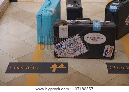 few travel bags suitcases luggage near check in line in a hotel lobby. all suitcases covered with stickers from different places all over the world
