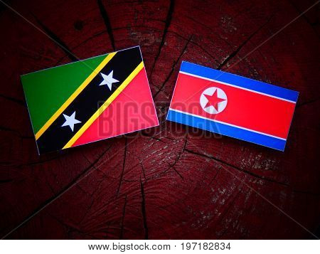 Saint Kitts And Nevis Flag With North Korean Flag On A Tree Stump Isolated