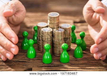 Close-up Of Hands Protecting The Coin Stack Surrounded With Green Figures On Wooden Desk