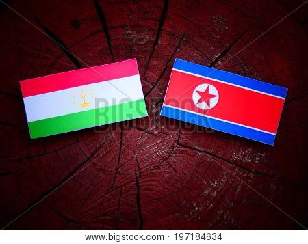 Tajikistan Flag With North Korean Flag On A Tree Stump Isolated