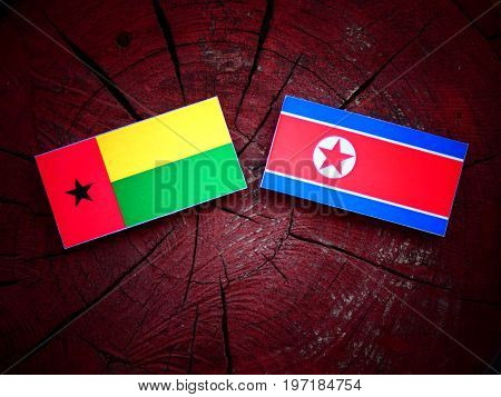 Guinea Bissau Flag With North Korean Flag On A Tree Stump Isolated