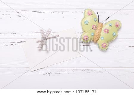 Decorative butterfliy and empty tag on vintage wooden background. Top view. Flat lay. Place for text.