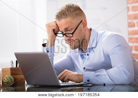 Contemplated Businessman Sitting With Laptop At Workplace