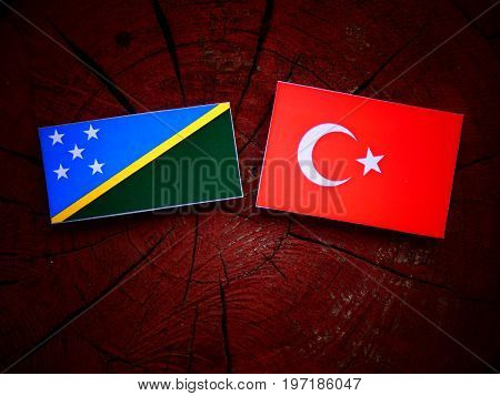 Solomon Islands Flag With Turkish Flag On A Tree Stump Isolated