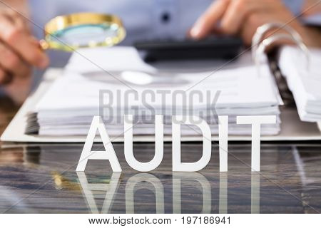 Close-up Of Financial Data Analyst With Audit Text On Glass Desk In Office