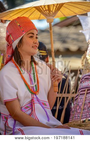 CHIANGMAI THAILAND - JANUARY 25 2015: Hill tribe girl holding red paper umbrella in parade of 22nd Traditional Skirt Fabric and The Indigenous Product and Culture Festival in Mae Chaem Chiangmai Thailand
