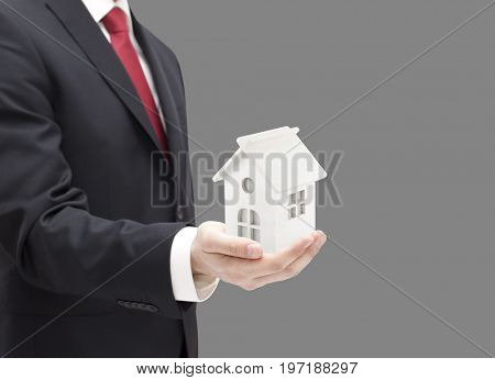 Businessman with white toy house miniature in hand