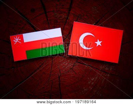Omani Flag With Turkish Flag On A Tree Stump Isolated