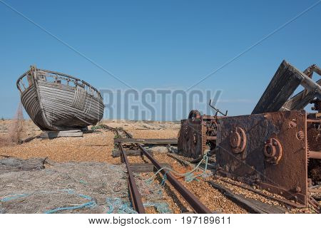 Old wooden fishing boat and a rusty winch on a beach