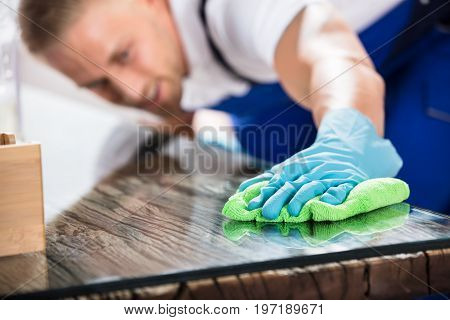 Close-up Of A Young Male Janitor Cleaning Desk With Green Cloth