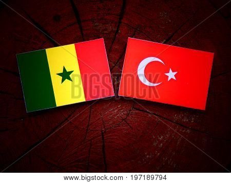 Senegal Flag With Turkish Flag On A Tree Stump Isolated