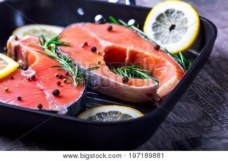 Steaks of raw salmon. Pieces of fish in a frying pan. Fish with herbs spices and lemon. Salmon is cooked for frying. Concept of a healthy diet