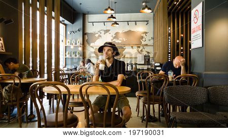 Istanbul Turkey - June 02 2017: Young man at Starbucks coffee shop in Istanbul. Starbucks Corporation is an American global coffee company and coffeehouse chain based in Seattle Washington.