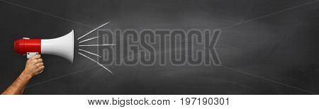 Hand holding megaphone over chalkboard background with copy space