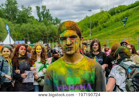 Moscow, Russia - June 3, 2017: Portrait of young guy with very serious face, stained with yellow, green and orange paint, standing on the background of people celebrating traditional summer Holi