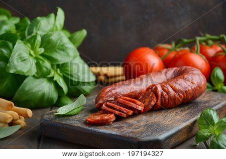 Chorizo sausage. Spanish traditional chorizo sausage with fresh herbs and tomatoes.