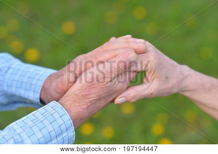 Close up view of senior couple holding hands together