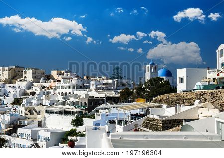 Fira, Thira town, Santorini, Cyclades islands, Greece. Beautiful view of the town with white buildings, blue church's roofs and many colored flowers.
