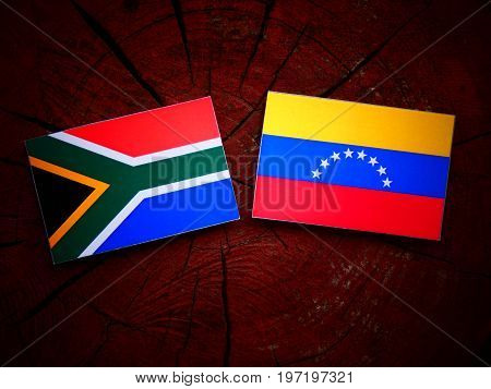 South African Flag With Venezuelan Flag On A Tree Stump Isolated