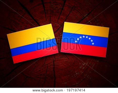 Colombian Flag With Venezuelan Flag On A Tree Stump Isolated