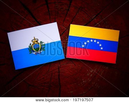 San Marino Flag With Venezuelan Flag On A Tree Stump Isolated