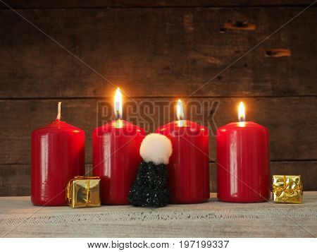Four red Advent candles on a rustic wooden background three candles burning third Advent Christmas concept nackground