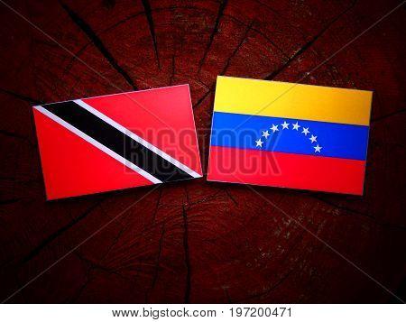 Trinidad And Tobago Flag With Venezuelan Flag On A Tree Stump Isolated