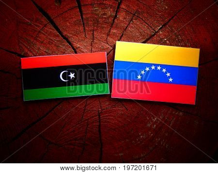 Libyan Flag With Venezuelan Flag On A Tree Stump Isolated