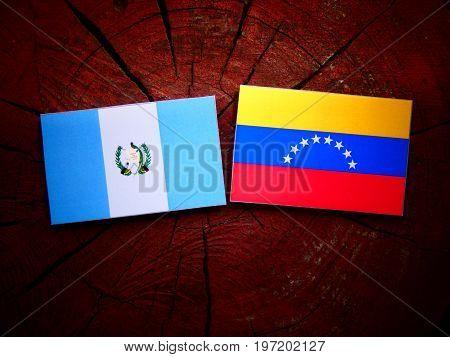 Guatemalan Flag With Venezuelan Flag On A Tree Stump Isolated