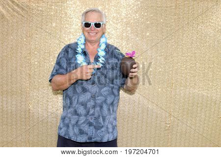 A man wearing a Hawaiian shirt, a blue lei, blue sun glasses and holding a plastic coconut drink cup with a straw stands in front of a gold sequin background and smiles in a photo booth.