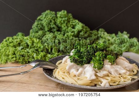Spaghetti with white sauce chicken breast kale leaves served in grey plate on wooden board fresh kale on the background