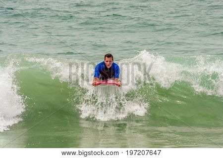 A man rides a wave at the beach on a boogie board. He looks like he is having a great time. He is wearing a wetsuit.