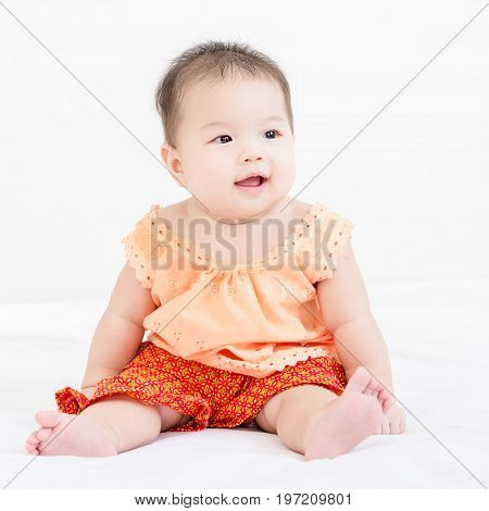 Portrait Of A Little Adorable Infant Baby Girl Sitting On The Bed And Looking To The Right Side