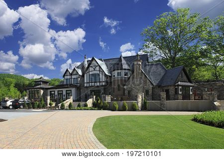 Huge Luxurious expensive farmhouse style mansion with long brick driveway, stone walls, and large patio