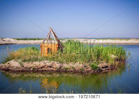 Unfinished wooden house for the birds - ducks or swans- on a small island in a pond. Waterfowl shelter made by human.