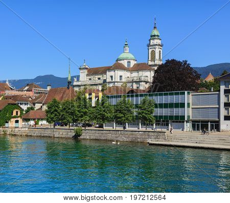 Solothurn, Switzerland - 10 July, 2016: the Aare river in the city of Solothurn, buildings along it, towers of the St. Ursus cathedral and mountains in the background. The city of Solothurn is the capital of the Swiss canton of Solothurn.
