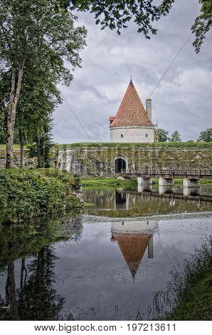 Tower of Kuressaare Castle reflected in the water of the moat on the island of Saaremaa Estonia