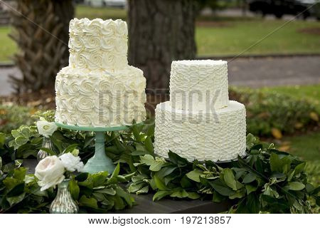 Pair of two tiered buttercream frosted wedding cakes at outdoor reception