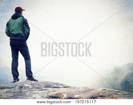 Film Effect. Young Man In Black Sportswear Is Sitting On Cliff's Edge And Looking To Misty Valley Be