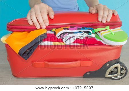 Woman hands packing stuff into suitcase at home. Travel and vacations concept. Suitcase with things for spending summer vacation things prepared for travel