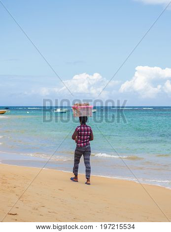 Local Salesman with goods on the head on the caribbean beach. Punta Cana, Dominican Republic