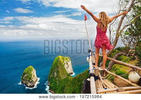 Family vacation lifestyle. Happy woman with raised in air hand stand at viewpoint. Look at beautiful beach under high cliff. Travel destination in Bali. Popular place to visit on Nusa Penida island