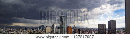 A panorama of Mexico City. Every afternoon rainstorms come in across the mountains around Mexico City in the summer, the rainy season.