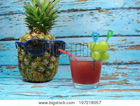 Pineapple fruit with blue  sunglasses drinks fruity cocktail/ Pineapple fruit with blue  sunglasses in front of scraped blue planks.