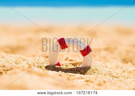 Miniature White And Red Lifebuoy In Sand At Beach