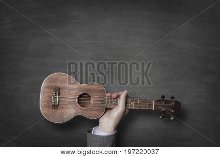 Cropped image of businessman's hand holding guitar against blackboard