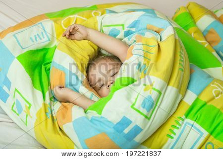 Childhood and happiness. Trust and tenderness. Small baby dreaming. Child sleep in bed. Sleepy baby in colorful blanket.