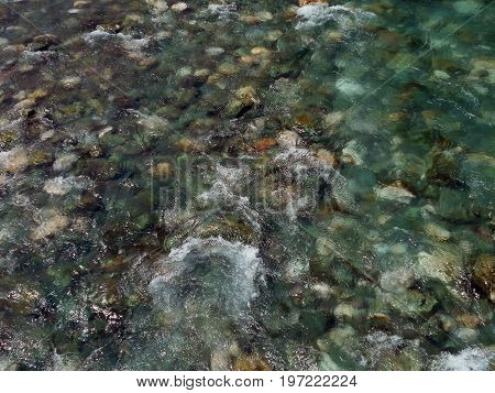 Clear and transparent water in the river, with pebbles on the riverbed
