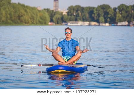 Portrait of young man doing yoga on sup board with paddle on water. Meditative lotus pose