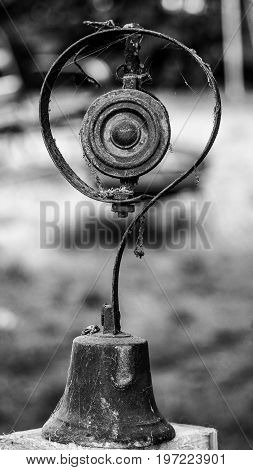 An antique service bell, some oxidation of the metal, in black and white on a piece of wood